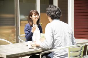 テラス席でテイクアウトランチを食べるミドルの男女の写真素材 [FYI04602016]