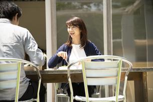テラス席でテイクアウトランチを食べるミドルの男女の写真素材 [FYI04602022]