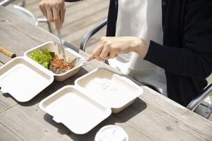 テラス席でテイクアウトランチを食べるミドルの女性の手元の写真素材 [FYI04602031]