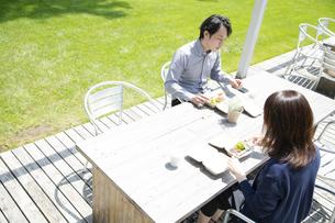 テラス席でテイクアウトランチを食べるミドルの男女の写真素材 [FYI04602036]