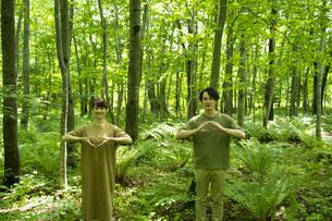 手話で「地球」を表現するミドルの男女の写真素材 [FYI04602226]