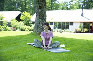 芝生の上でリラックスする女性の写真素材 [FYI04602480]