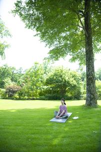 芝生の上でリラックスする女性の写真素材 [FYI04602483]