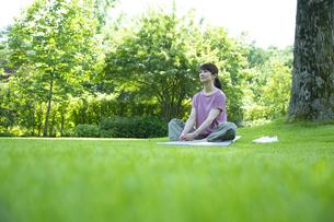 芝生の上でリラックスする女性の写真素材 [FYI04602486]