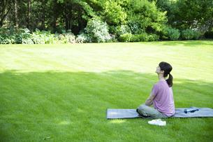 芝生の上でリラックスする女性の写真素材 [FYI04602489]