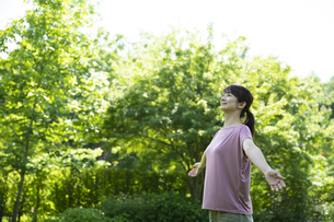 新緑の中深呼吸する女性の写真素材 [FYI04602498]