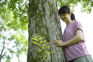 木に寄り添うミドルの女性の写真素材 [FYI04602501]