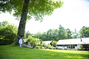 芝生の上で仕事をするミドルの男性の写真素材 [FYI04602509]