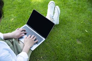 芝生の上で仕事をするミドルの男性の手元の写真素材 [FYI04602512]