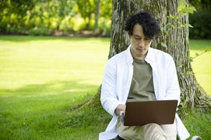 芝生の上で仕事をするミドルの男性の写真素材 [FYI04602513]