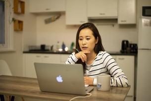 家からリモート会議に参加している女性の写真素材 [FYI04602536]