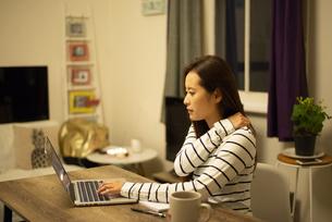 パソコンの前で肩を触っている女性の写真素材 [FYI04602566]