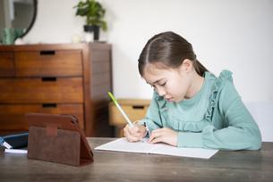 家でタブレットを置いて勉強をしている女の子の写真素材 [FYI04602592]