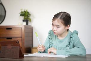 家でタブレットを見ながら勉強をしている女の子の写真素材 [FYI04602593]