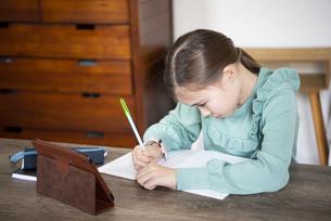 家でタブレットを置いて勉強をしている女の子の写真素材 [FYI04602594]