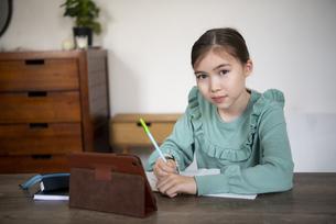 家でタブレットを置いて勉強をしている女の子の写真素材 [FYI04602596]