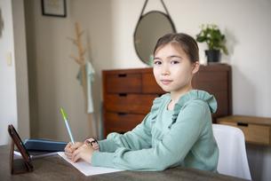 家でタブレットを置いて勉強をしている女の子の写真素材 [FYI04602597]