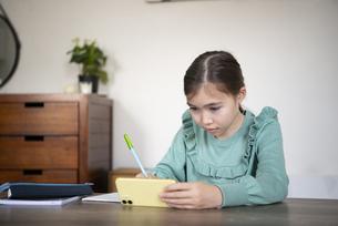 家でスマホを見ながら勉強をしている女の子の写真素材 [FYI04602598]