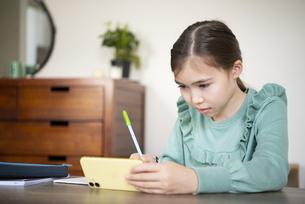 家でスマホを見ながら勉強をしている女の子の写真素材 [FYI04602599]