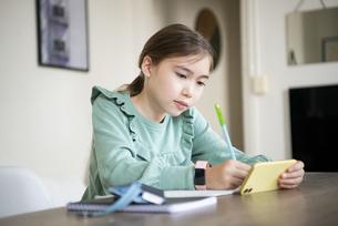 家でスマホを見ながら勉強をしている女の子の写真素材 [FYI04602600]