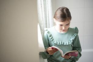 窓辺で本を読んでいる女の子の写真素材 [FYI04602714]
