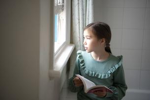 窓辺で本を持って外を眺めている女の子の写真素材 [FYI04602716]