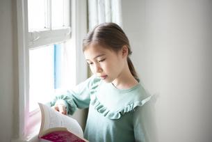 窓辺で本を読んでいる女の子の写真素材 [FYI04602718]