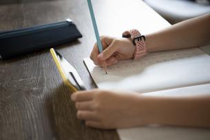 スマホを持って勉強をしている女の子の手元の写真素材 [FYI04602746]