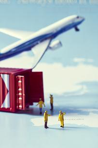 世界地図の上のミニチュアの飛行機とコンテナと人々の写真素材 [FYI04602764]