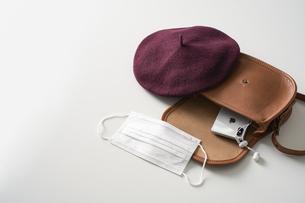 白い机の上のバッグと帽子とマスクの写真素材 [FYI04602787]