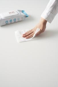 机の上を除菌する女性の手の写真素材 [FYI04602796]