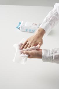 除菌シートで手を拭く女性の手元の写真素材 [FYI04602798]