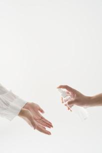 除菌スプレーを持つ人と両手を差し出す人の写真素材 [FYI04602800]