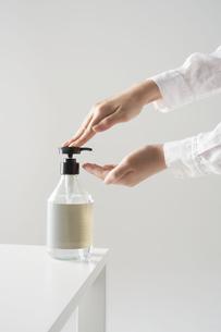 机の上の除菌ポンプを使う女性の手元の写真素材 [FYI04602802]