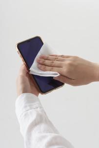 スマートフォンを除菌シートで拭く女性の手元の写真素材 [FYI04602804]