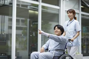 散歩する車椅子の患者と看護師の写真素材 [FYI04602816]