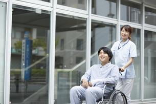 散歩する車椅子の患者と看護師の写真素材 [FYI04602817]
