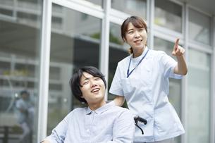 散歩する車椅子の患者と看護師の写真素材 [FYI04602818]