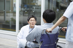 車椅子の患者に話しかける男性医師の写真素材 [FYI04602820]