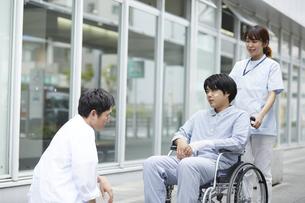 車椅子の患者と看護師に話しかける男性医師の写真素材 [FYI04602821]