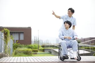 散歩する車椅子の患者と看護師の写真素材 [FYI04602826]