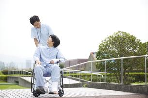 散歩する車椅子の患者と看護師の写真素材 [FYI04602827]