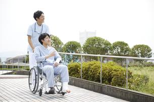 散歩する車椅子の患者と看護師の写真素材 [FYI04602829]