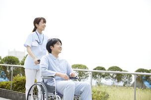 散歩する車椅子の患者と看護師の写真素材 [FYI04602831]