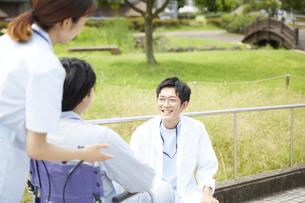 車椅子の患者と看護師に話しかける男性医師の写真素材 [FYI04602833]