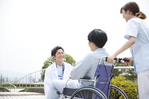 車椅子の患者と看護師に話しかける男性医師の写真素材 [FYI04602834]