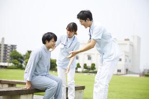 病院の庭で患者を補助する看護師の写真素材 [FYI04602837]