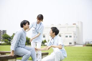 病院の庭で話す患者と看護師の写真素材 [FYI04602838]