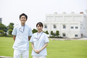 芝生の背景と笑顔の看護師の写真素材 [FYI04602841]