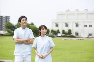 芝生の背景と真剣な顔の看護師の写真素材 [FYI04602843]